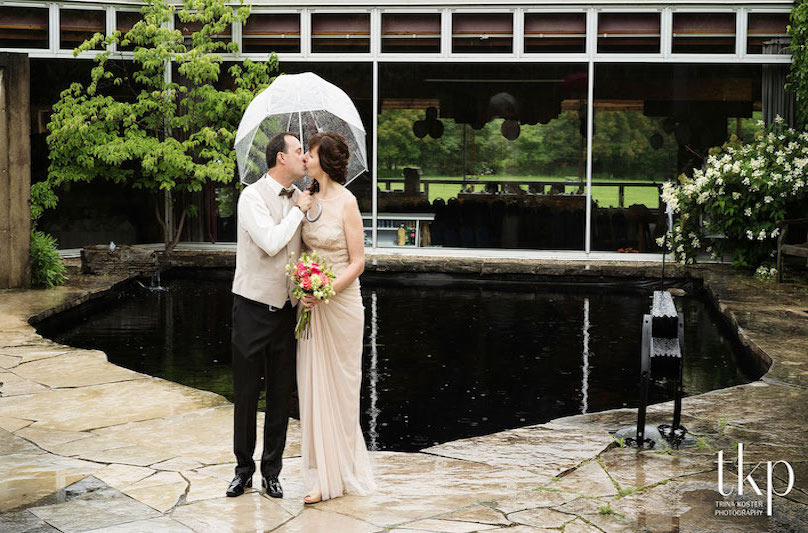 Bridge and groom kiss under an umbrella in front of the Arboretum Centre's reflecting pool