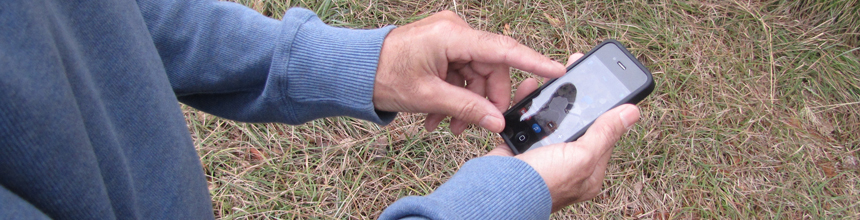 person using phone to find geocache